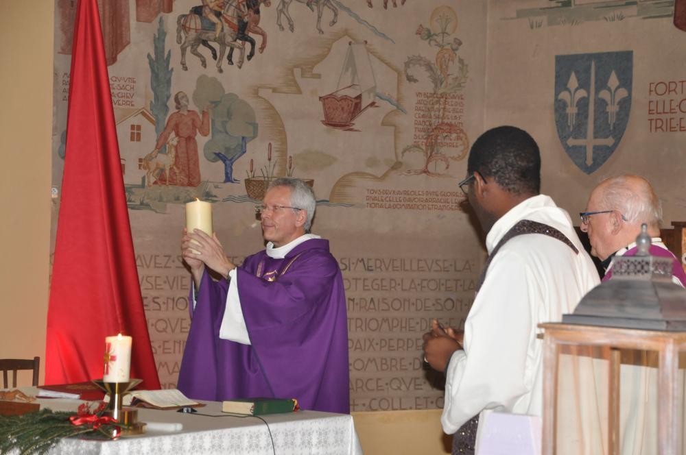 Pfr. Barthelemy segnet die Gemeinde mit dem Friedenslicht
